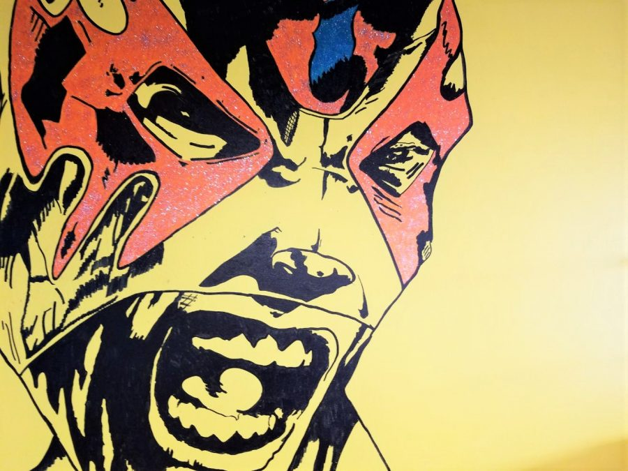 One of the several luchadors pictured on the brightly colored walls of Mucha Lucha Taco Shop.