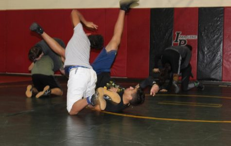 Sophomores Deshawn Newman, left, and Angel Acevedo III, right, practice their wrestling skills during early morning practice before school.